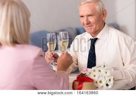 To the love of my life. Gallant handsome elderly gentleman making a toast to beauty of his woman while sitting at the table in a cozy restaurant during celebration