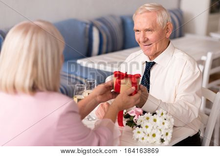 You might like it. Courteous good looking senior gentleman cheering his pretty lady by bringing her a gift while they are celebrating their anniversary in a restaurant