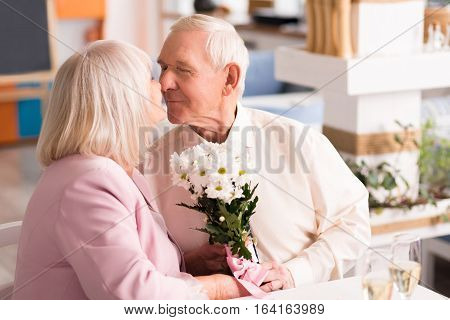 One more kiss. Two beloved wonderful senior people expressing their overflowing emotions during the celebration on their engagement in a restaurant