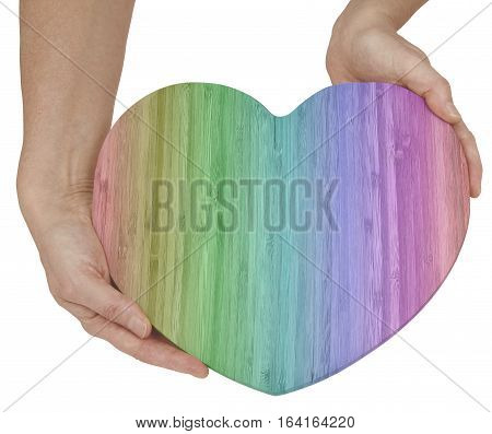 Rainbow colored Wooden Love Heart Message board -  female holding a large blank Bamboo Wooden Heart shaped board with rainbow coloring isolated on a white background
