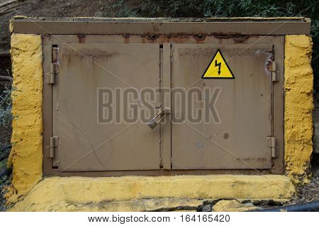 Old yellow electricity junction box - outdoors