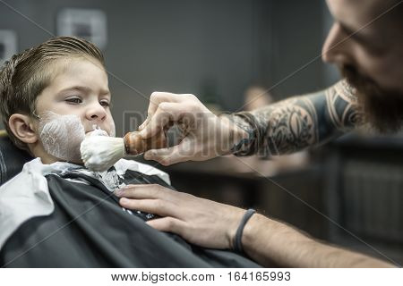 Dreaming kid in a black salon cape in the barbershop. Bearded barber with a tattoo applies shaving foam with the help of the shaving brush on his face. Closeup low aperture photo. Horizontal.