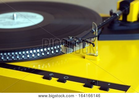 Turntable in silver case playing a vinyl record with red label. Horizontal photo isolated on black background closeup