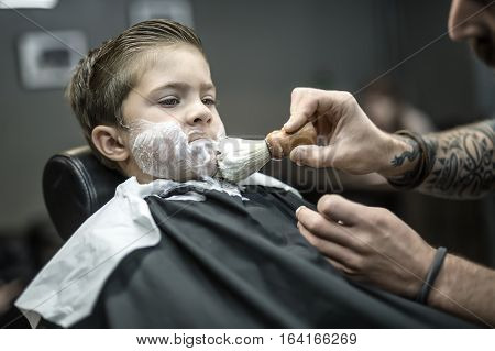 Serious kid in a black salon cape in the barbershop. Barber with a tattoo applies shaving foam with the help of the shaving brush on his face. Closeup low aperture photo. Horizontal.