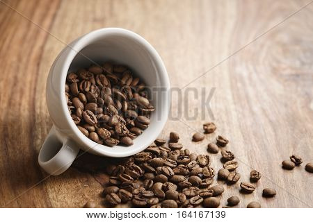 overturned cappuccino cup with roasted coffee beans on wood table, with copy space