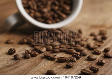 overturned cappuccino cup with roasted coffee beans on wood table, closeup photo