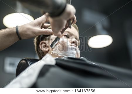 Thoughtful kid with a shaving foam on the face in the barbershop. He wears a black salon cape. Barber is shaving boy's face with the help of the straight razor. Low aperture closeup photo. Horizontal.