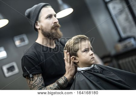 Stylish little boy in a black salon cape in the barbershop. Bearded barber with a tattoo in a black cap does kid the hairstyle. Wide aperture closeup photo. Horizontal.