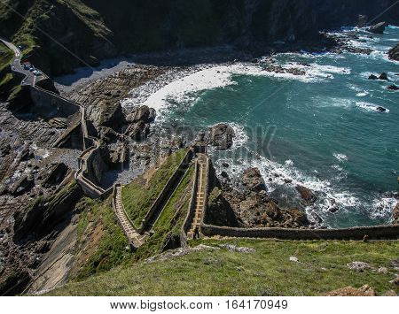 Gastelugache -  island on  coast of  Bay of Biscay belonging to  municipality of Bermeo, Basque Country.  Island is connected to  mainland by  man-made bridge that goes into  winding staircase that spans 237 degrees.