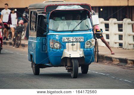 NEGOMBO, SRI LANKA. July 20, 2016: Tuk Tuk on the road in Negombo, a town near the capital Colombo in Sri Lanka. Typical national car. Tuk-tuk auto rickshaw. Bajay or Bajaj.