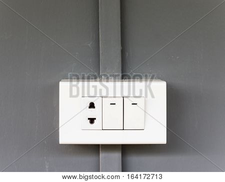 Plastic electrical socket with lighting switch on the house wall.