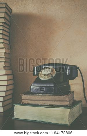 Old black phone standing on telephone directories next to a stack of books