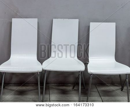 Dirty white chair with metal leg near the office wall.