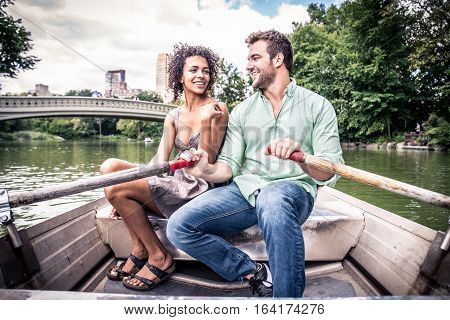 Happy couple having fun on a boat in Central Park - Interracial couple of tourists sighseeing Manhattan