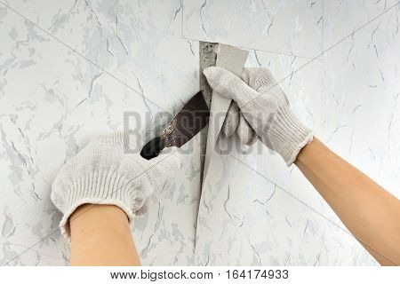 removing old wallpapers from wall with spatula during repair