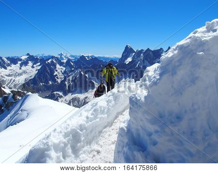 Alpinists and mountaineer climber in french ALPS on high alpine mountains range landscape on AIGUILLE DU MIDI at CHAMONIX MONT BLANC in FRANCE with clear blue sky in warm sunny summer day, EUROPE on JULY.
