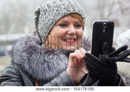 KACHANIVKA UKRAINE - 25 November 2016: Woman in coat take photo with smart mobile phone outdoors at autumn day
