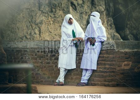 SIGIRIYA, SRI LANKA. July 20, 2016: Two Arab women are relaxed and talking to each other at Sigiriya in Sri Lanka. Wear the typical dress of Muslim and Arab culture.
