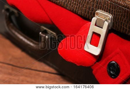 Clothes in old suitcase red coat. Love travel