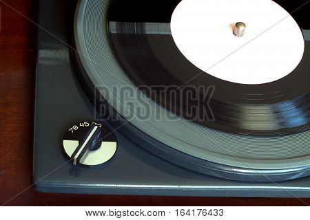 Part of old vintage three speed record player playing vinyl record with white label. Horizontal top view closeup