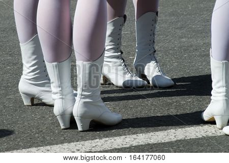 Attractive legs of young women in white boots standing on street