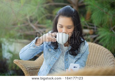 businesswoman reading news or texting sms on smartphone while drinking coffee on break from work