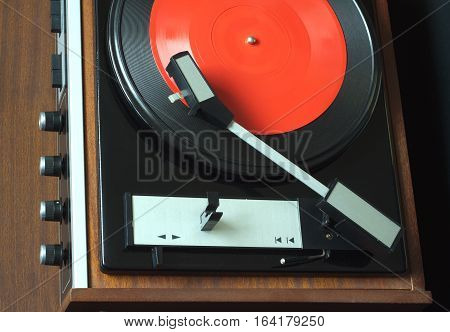 Old vintage vinyl record player in brown wooden case playing red flexible LP record. Top view horizontal photo closeup