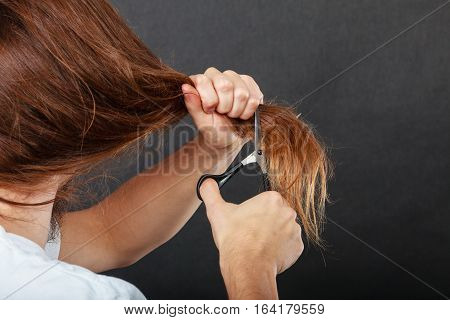 Change of look. Barber and hairdresser. Male hands with scissors trimmers cutting long brown hair.