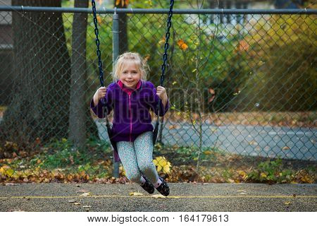Adorable school age girl sitting on swing at park during fall autumn season