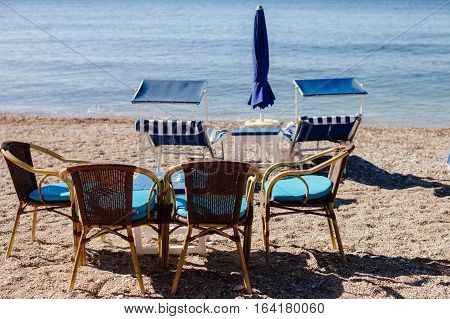 beach cafe and sunbeds. Blue sea water.