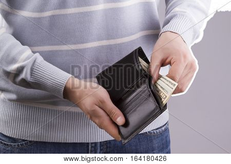 man holding a black wallet with money