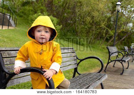 Adorable toddler boy wearing rain jacket sitting on bench outside