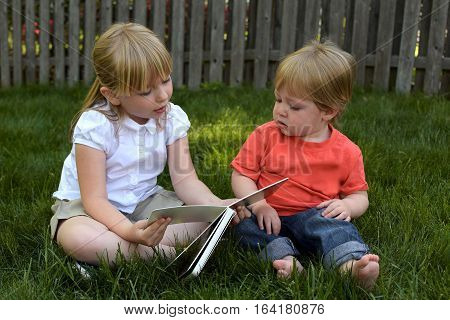 Siblings story time big sister reading to little brother outside