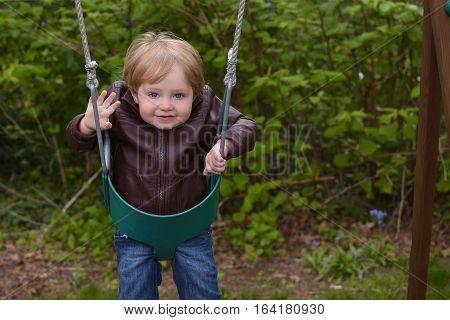 adorable toddler boy child sitting in swing during spring season