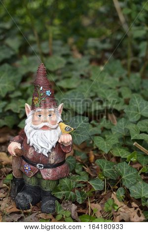 red garden gnome holding bird and sitting in ivy