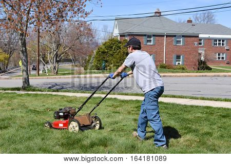 young adult man mowing front yard lawn