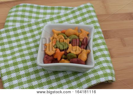 colorful rainbow goldfish crackers in bowl on napkin on wooden cutting board