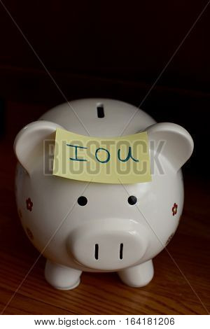 piggy bank with post it note saying iou on it
