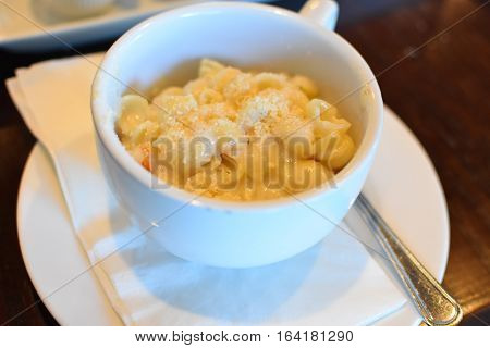 white bowl of hot mac n cheese on top of napkin