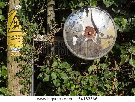 Finmere Oxfordshire United Kingdom January 05 2017: Broken traffic safety convex driveway mirror attached to wooden electricity pylon on Fulwell Road Finmere Buckingham.