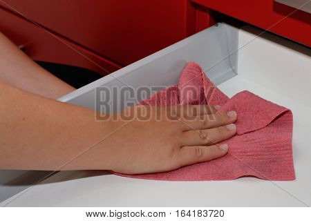 Person cleans drawer with damp sponge - closeup