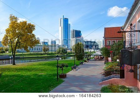 MINSK BELARUS - OCTOBER 1 2016: Unidentified people are walking in Trinity Suburb on sunny autumn day. On background - business center Royal Plaza and DoubleTree By Hilton Hotel Minsk
