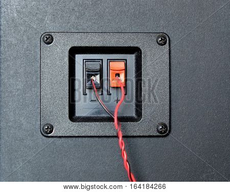 Red and black twisted wire connected to cable connection socket on rear side speaker system box front view closeup
