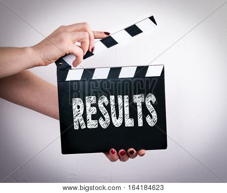 Results. Female hands holding movie clapper. Gray background