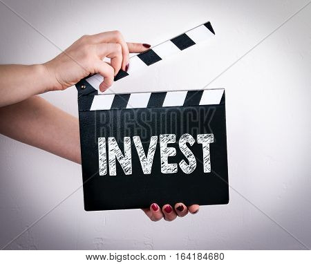 Invest. Female hands holding movie clapper. Gray background