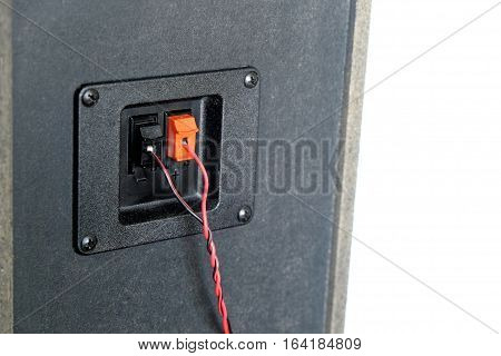 Red and black twisted wire connected to cable connection socket on rear side speaker system box side view vertical photo isolated closeup