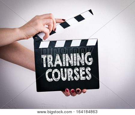 Training Courses. Female hands holding movie clapper.