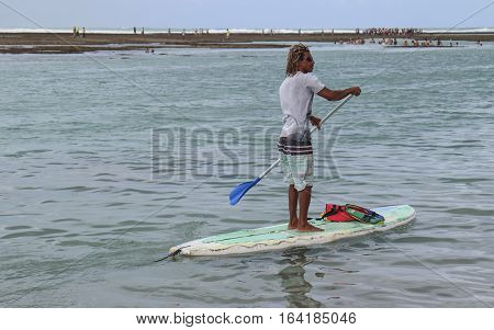 Pernambuco Brazil July 6 2016: An unidentified stand up paddle practitioner in Chicken Beach in Ipojuca City near barrier reef northeast Brazil