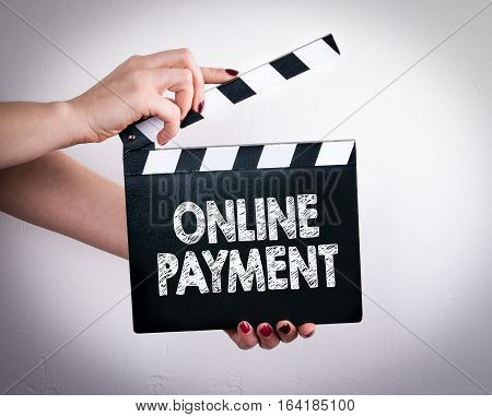 Online Payment. Female hands holding movie clapper.
