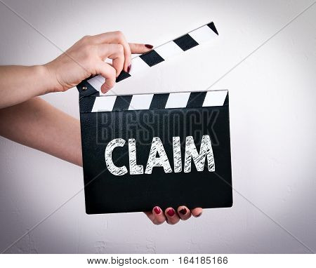 Claim. Female hands holding movie clapper. Gray background